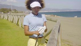 Attractive female golfer leaning on a wooden fence stock footage