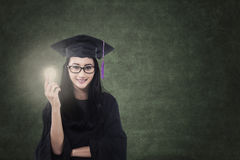 Attractive female graduate holding lit bulb in class Royalty Free Stock Image