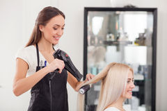 Attractive Female Hairstylist Is Working With Joy Stock Photo