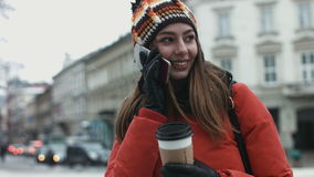 Attractive female in her 20s using cellphone outdoors. Young woman talking on telephone in the european city center. Attractive female in her 20s using stock video footage