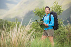 Attractive female hiker with backpack holding a map Royalty Free Stock Photography