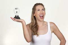 Attractive female holding a bulb and looking at it Stock Images