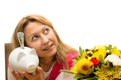 Attractive female holding a piggy bank. In her hands Stock Image