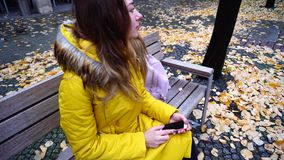 Attractive female holding smartphone and browsing photos, sitting on bench in city on street in autumn afternoon. Grand Young woman thumbs and browses on gadget stock video