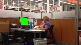 Attractive female Homedepot worker typing information with green screen computer stock video footage