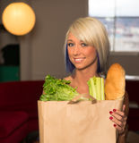 Attractive Female Homemaker Sets Grocery Bag on Counter Stock Image