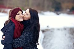Attractive female kissing her friend on the cheek Stock Image