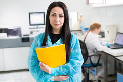 Attractive female lab worker making medical research in modern laboratory. Scientist holding documents folder with Royalty Free Stock Image