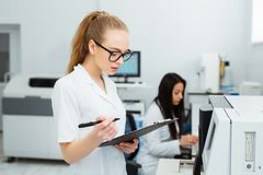Attractive female lab worker making medical research in modern laboratory. Scientist holding documents folder with Royalty Free Stock Photo