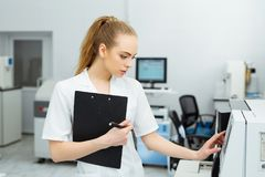Attractive female lab worker making medical research in modern laboratory. Scientist holding documents folder with Royalty Free Stock Images