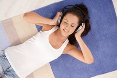 Attractive female laying on floor enjoying music Stock Photo
