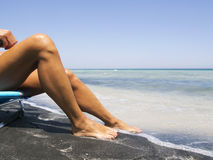 Attractive female legs relaxing on a beautiful   beach. Attractive female legs relaxing on a beautiful white and black beach Royalty Free Stock Photography