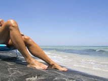 Attractive female legs relaxing on a beautiful  beach. Attractive female legs relaxing on a beautiful white and black beach Stock Images