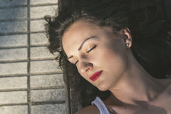 Attractive female lying on park bench Royalty Free Stock Image