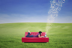 Attractive female lying on red sofa and typing e-mail outdoor Royalty Free Stock Image