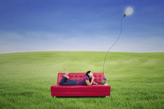 Attractive female lying on red sofa under lamp outdoor Royalty Free Stock Photos