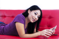 Attractive female lying on sofa with e-tablet - isolated Royalty Free Stock Images