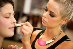 Attractive female make up artist at work. Stock Images