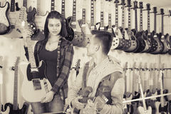 Attractive female and male teenagers examining electric guitars Royalty Free Stock Photography