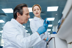 Attractive female medical worker looking at her colleague. Examining reaction. Very attentive technician pressing lips and doing blood analysis while sitting in stock photos