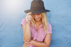 Attractive female model looking happy. Portrait of smiling young woman with hat against blue wall. Attractive female model looking happy Royalty Free Stock Image