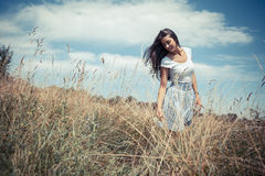 Attractive female model in nature. Attractive female model in  white dress.She walking trough meadow Stock Photography
