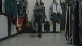 Female model walks in a store with high heels and holds her phone in the jeans back pocket while looking for new clothes -. Attractive female model walks in a stock footage
