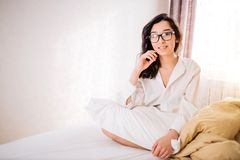 Beautiful Positive woman sitting in bed in morning. Attractive female model wearing nightwear holding white pillow. Indoor photo of carefree woman with dark hair stock photos