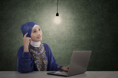 Attractive female muslim with laptop has idea Royalty Free Stock Image