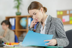 Attractive female office worker checks something in folder Stock Image