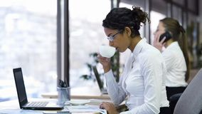 Attractive female office worker drinking cup of coffee and reading charts. Stock footage Royalty Free Stock Image