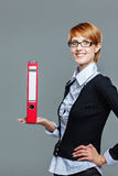 Attractive female office worker holding folder Stock Photo