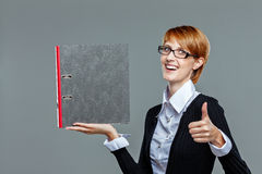 Attractive female office worker holding folder and showing thumb up Royalty Free Stock Photo