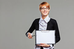 Attractive female office worker presenting a clipboard and pointing with a pen. Isolated on grey Stock Photography