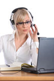 Attractive female operator with headset working Royalty Free Stock Image
