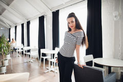 Attractive female owner of a modern cafe standing near wooden table with huge windows on the background. Beautiful woman Royalty Free Stock Image