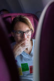 Attractive female passanger watching in-flight entertainment. stock images