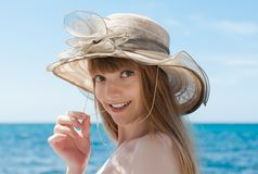 Attractive female person in broad-brim hat looking at camera smiling. Portrait of girl in beach hat against sea. Attractive female person in broad-brim hat stock images