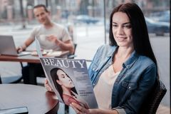 Attractive female person reading glossy magazine Royalty Free Stock Photography