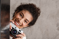 Attractive female photographer holding camera, looking out over beige background. Royalty Free Stock Images