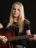Attractive female playing acoustic guitar Stock Photo