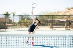 Attractive female playing tennis on court. Good looking female tennis player training on the tennis court, hitting the ball overhead Royalty Free Stock Photos