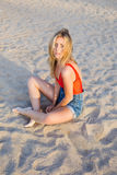 Attractive female posing for the camera sitting on the sand Royalty Free Stock Images