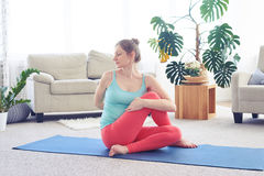 Attractive female practicing seated twist pose Stock Photos