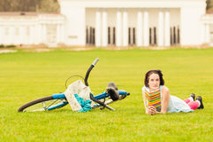 Attractive female reading a book near vintage bicycle. In the park in her free time Royalty Free Stock Images