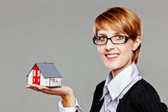 Attractive female real estate agent presenting a detached house model and smiling friendly to the camera Stock Photography