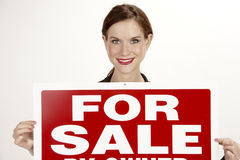 Attractive Female Realtor Holds up the For Sale Sign. For Sale by Owner sign held by beautiful female Royalty Free Stock Photography