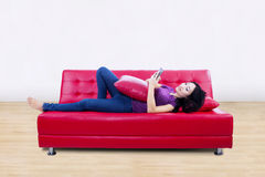 Attractive female on red sofa reading e-book at home Royalty Free Stock Image