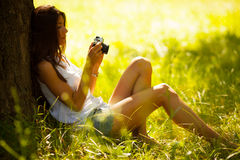 Attractive female relaxing. In nature.Holding camera Royalty Free Stock Image