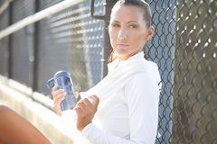 Attractive female resting. Against a chain link fence Royalty Free Stock Image